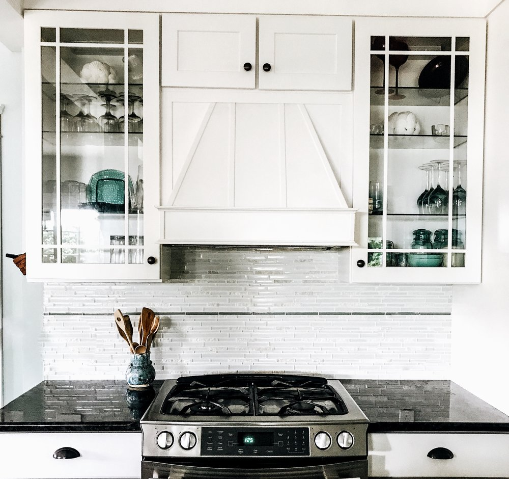 Lake House Kitchen Decor Ideas. White Kitchen For Summer Lake House. White kitchen with a white hood and glass cabinet doors. Glass tile backsplash in lake house kitchen.