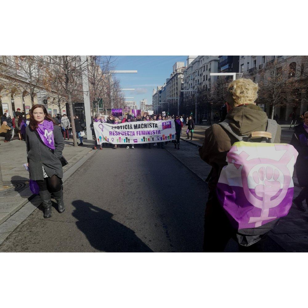 Dune Solanot fotografiando con la bandera no binaria y el símbolo transfeminista la manifestación del 25N, Día Contra la VIolencia Machista en Zaragoza.