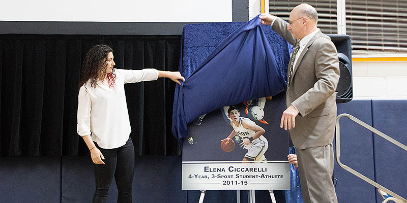 Sister Elena Theresa Ciccarelli unveils the plague with Gallaudet University Athletic Director Michael Weinstock, which is now up on the wall next to Alumna Sister Ronda Jo Miller's retired basketball jersey at Field House. © GALLAUDET ATHLETIC DEPARTMENT.