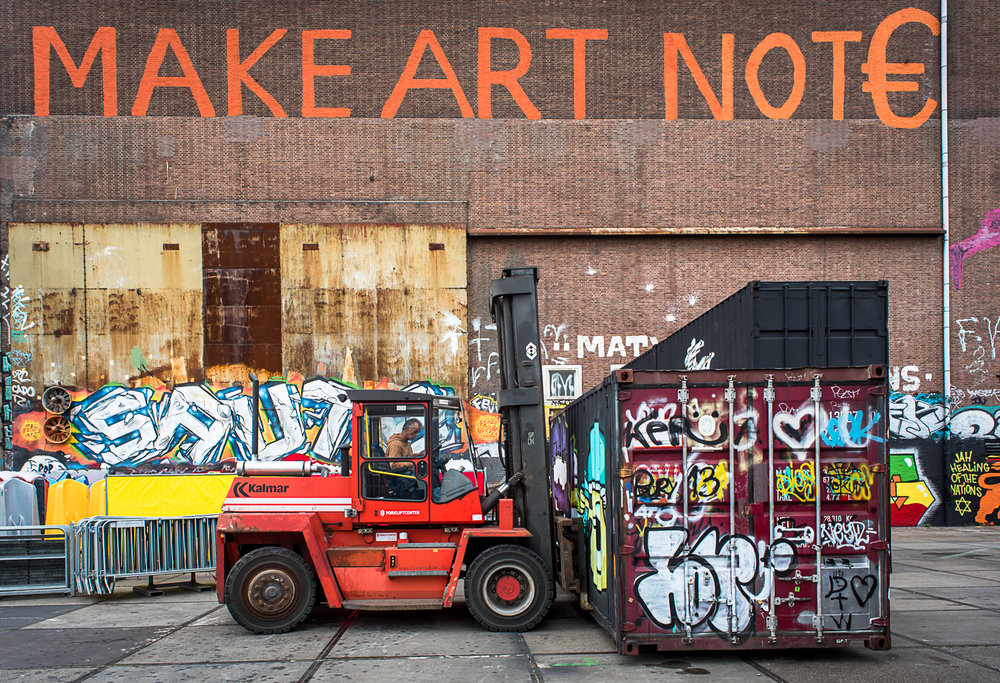 "Container boxes being moved to form a venue for a street art festival in a few hours. The shipping containers have many uses, including a canvas. ""Make art not €,"" prominently displays on a massive wall of one of the warehouses."