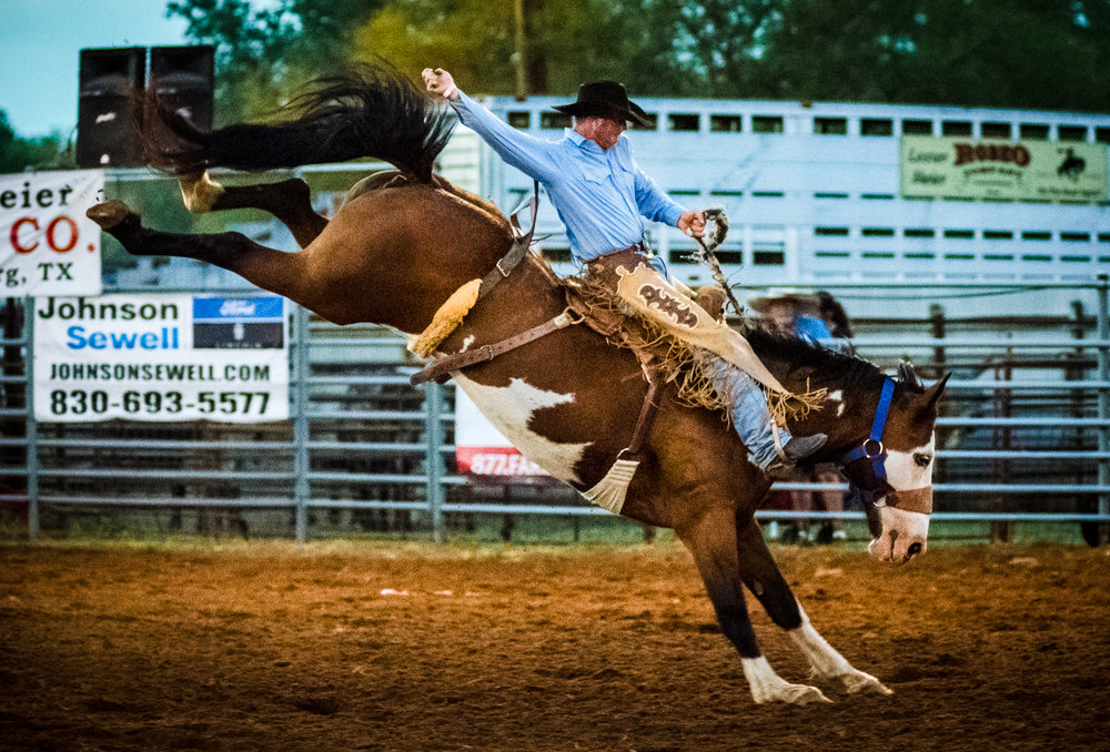 A cowboy flailing an arm on an unsurmountable bucking bronco forms a universal illustration of the romanticized American hero. Johnson City Rodeo 2017.