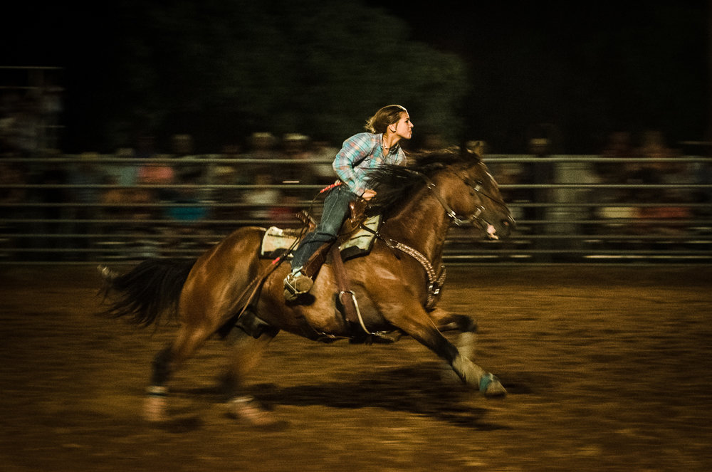 Barrel racing is the primary competitive rodeo event for women, where a cloverleaf pattern is completed around three barrels for the fastest time. Johnson City Rodeo 2017.