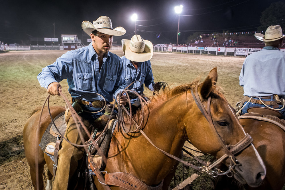 A ranch team just about to start a timed roping event. The beauty of local rodeos is the access and proximity one has to riders and animals. A five second prayer and off they go. Bandera Rodeo 2017.