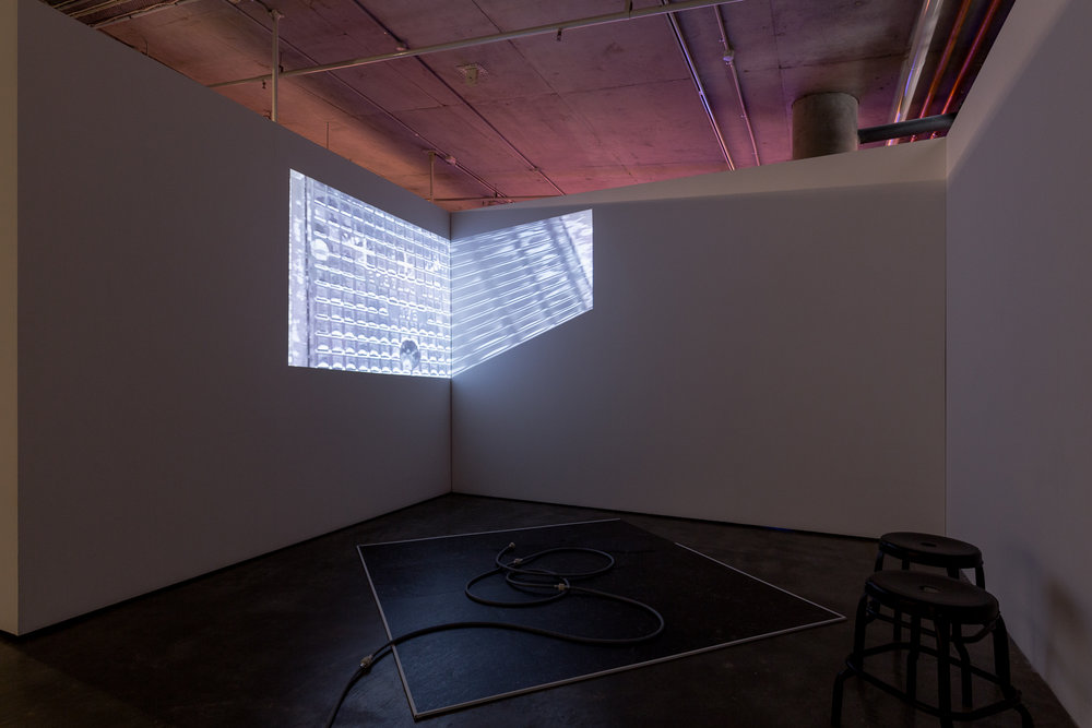 L > R    wetness quartet  . 2017. (install view). single-channel video. colour. sound. 00:34:18 loop  https://vimeo.com/246082006    this is that hose  . 2017-18. (install view). vinyl, particle board, rubber hose, water, stools. dimensions variable