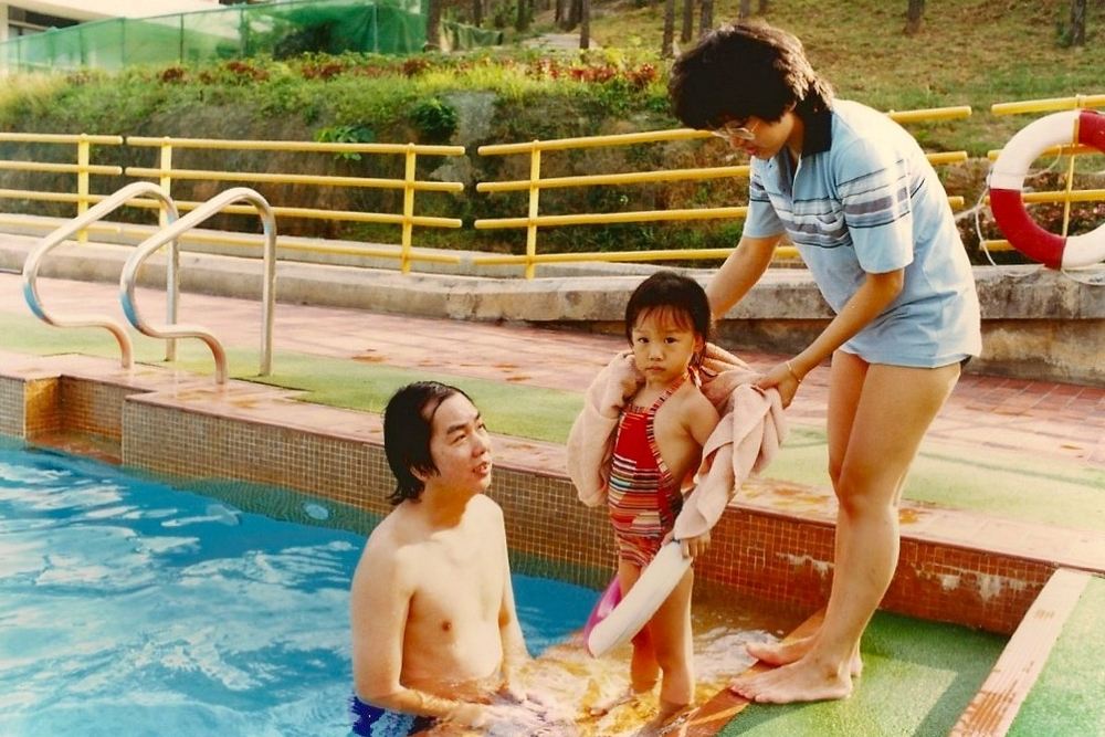 Child playing in swimming pool with parents - Sunday Kind of Love