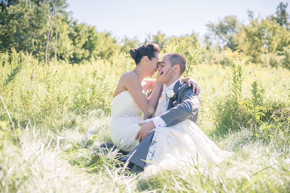 Bride and groom sitting in the middle of a sun lit field
