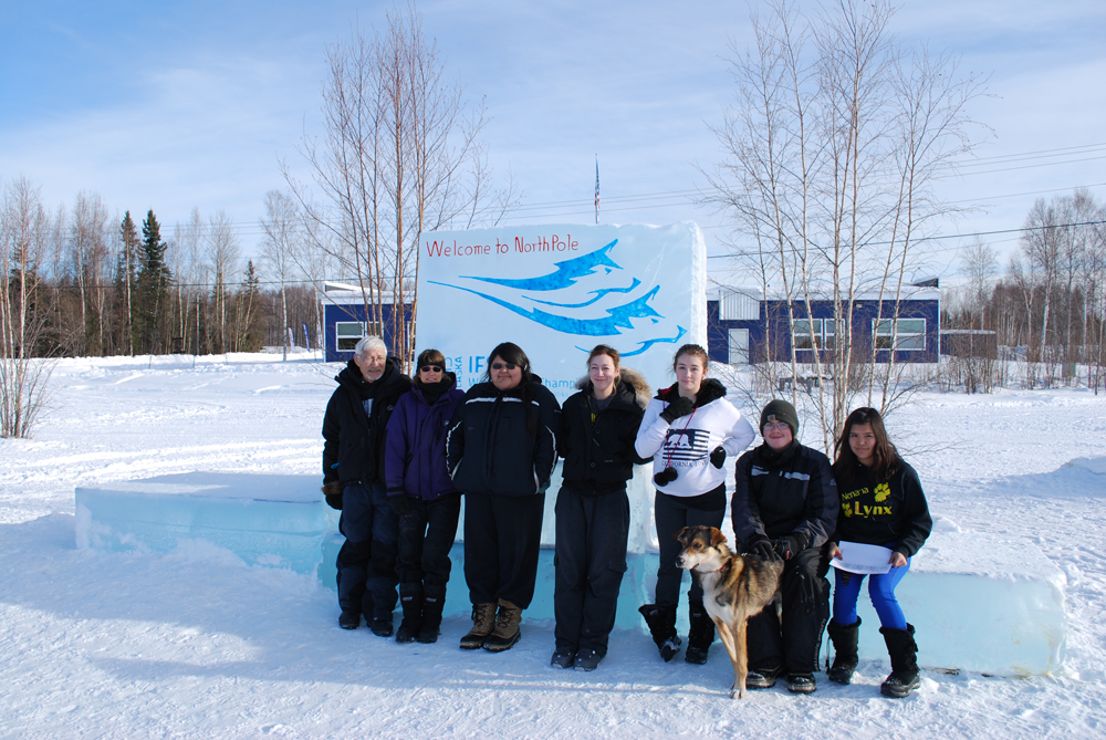 "(Left to Right) George Attla II, Kathy Turco, Dustina Sam, Shay Attla, Jazmine Vent, Thomas Henry with ""Happy"", and Courtney Agnes finish up with an intense three days of participating in the Junior North American Sled Dog Races, 2013. Photo by Angela Gonzalez"