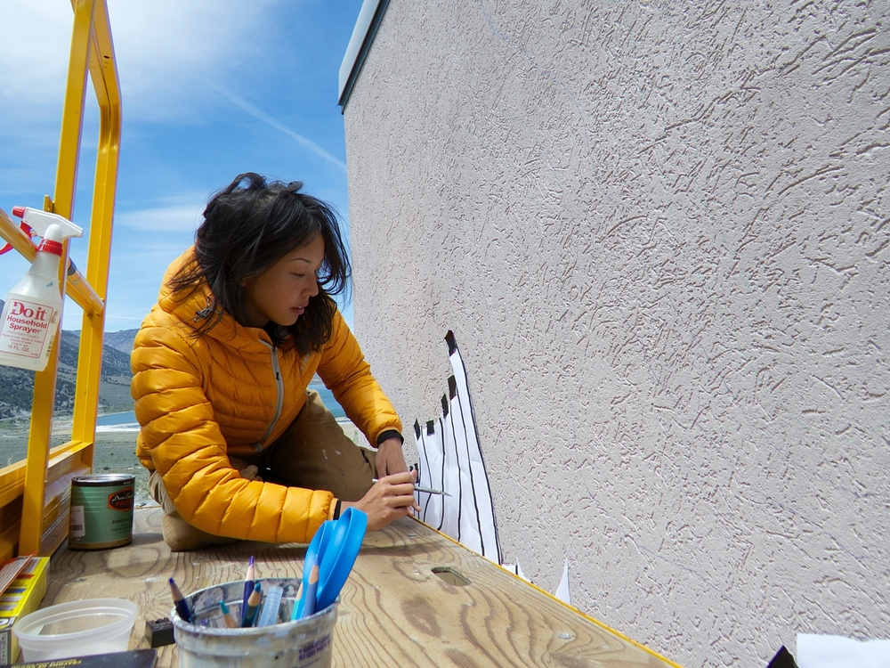 Jane Kim, working on the  Migrating Mural  project, the Sierra Nevadas behind her. Photo courtesy of Ginnie Chadwick.