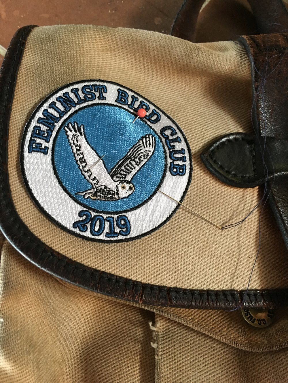 Sewing this year's Feminist Bird Club patch on my birding field bag.