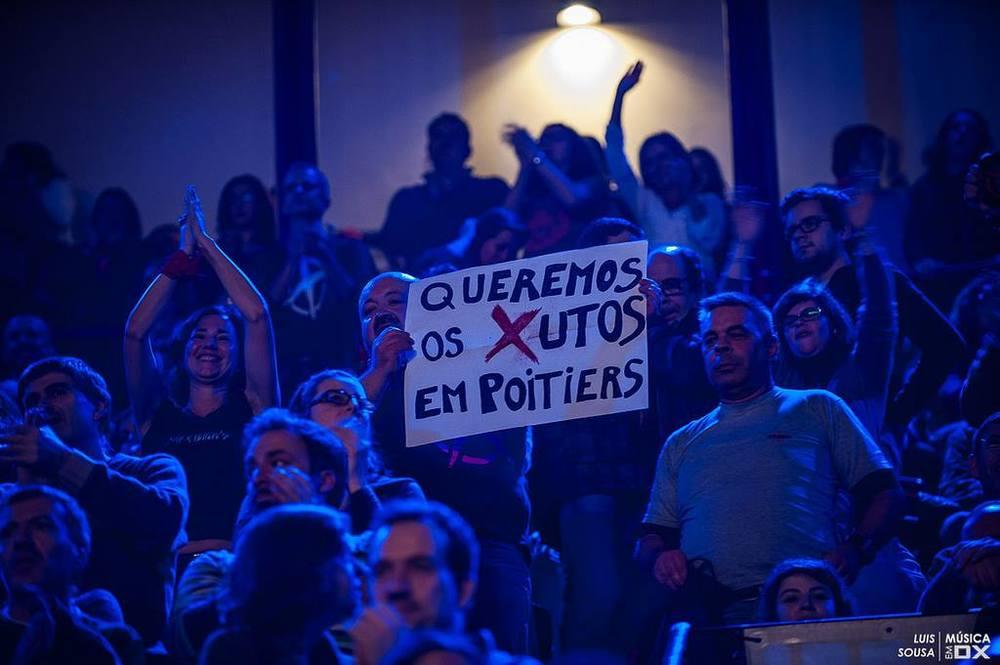 """Arlindo avec son affiche """"Queremos os Xutos em Poitiers"""" lors d'un concert du groupe à Lisbonne."""