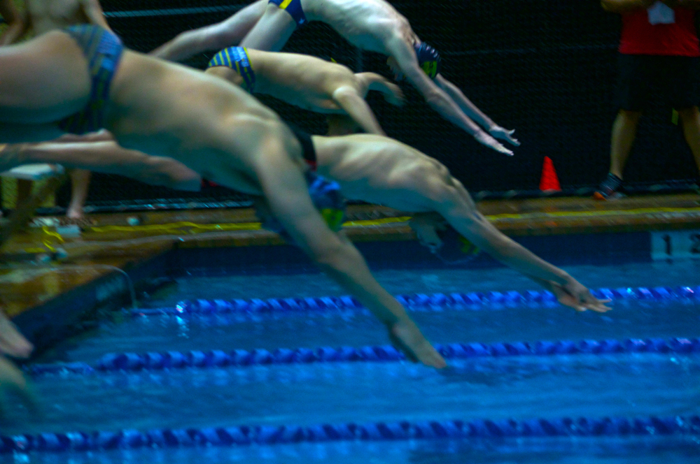 Athletes from St. Mark's, Hockaday and Greenhill dive into the water during the annual time trials hosted by the school.