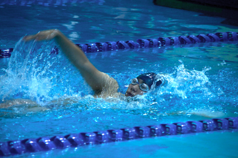 Slashing at the water, junior Jacob Hum competes in the 50 meter backstroke during the Dec. 1 time trials.
