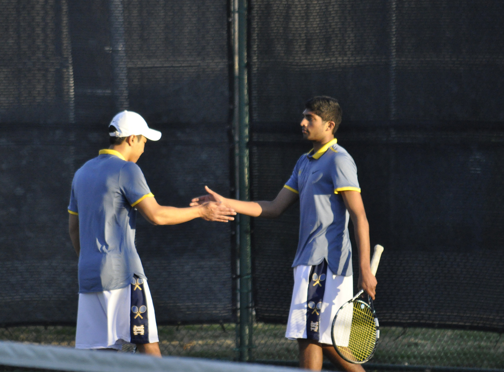 Seniors Albert Thieu and Anvit Reddy high five after winning a point during their Feb. 26 match against Highland Park. The duo went on to win the match against Henry Smith and Jordan Morris 6-2, 3-6, 6-2.