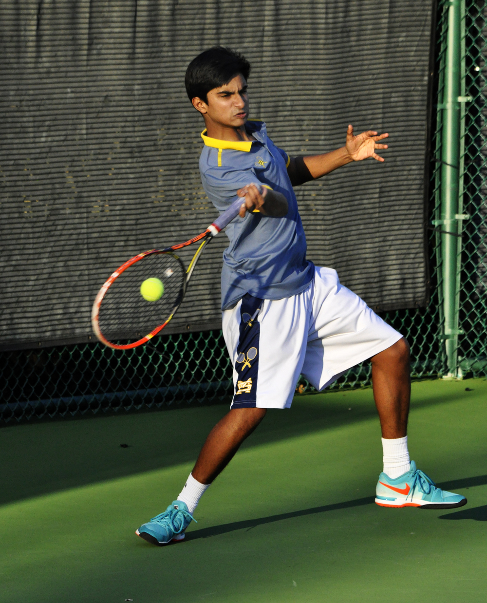 Fully loaded with a powerful forehand, junior Gopal Raman makes contact with the tennis ball during his Feb. 26 doubles match against Highland Park.