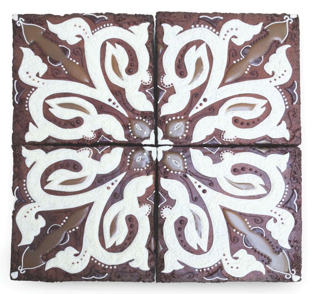 Chocolate brownie tiles decorated with hand-piped white chocolate, salted caramel sauce and dark chocolate.
