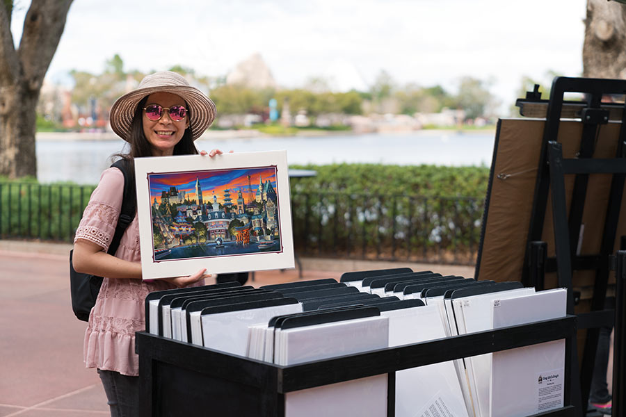 Thaneeya at Epcot's 2018 International Festival of the Arts, holding a print of a painting by artist Greg McCullough