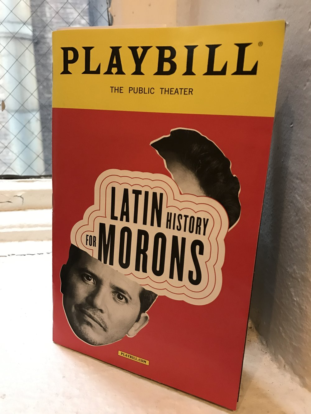 [Image of playbill cover on a window sill: Leguizamo's head split at his forehead with the words Latin History for Morons coming out of the opening.]