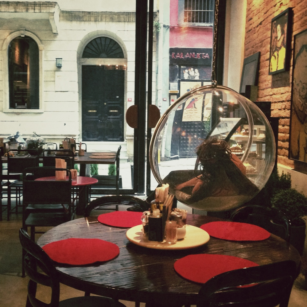 A woman dreamily sways and sings in a bubble swing as she plays with her dreadlocks at Nikol's chic cafe in Galata, a vibrant bohemian neighborhood.