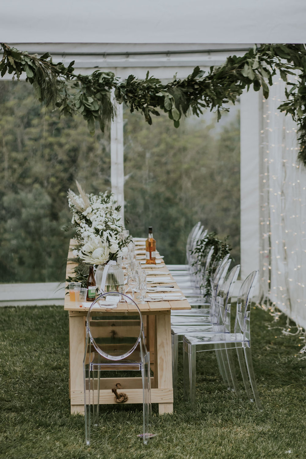 Wedding Marquee & Furniture Hire. Wooden Trestle Table and Ghost Chairs at Reception, Tauranga.