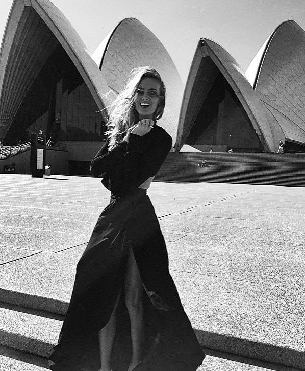 Me, trying not to flash my undies on a windy day, at the Sydney Opera House, in a very high split skirt.