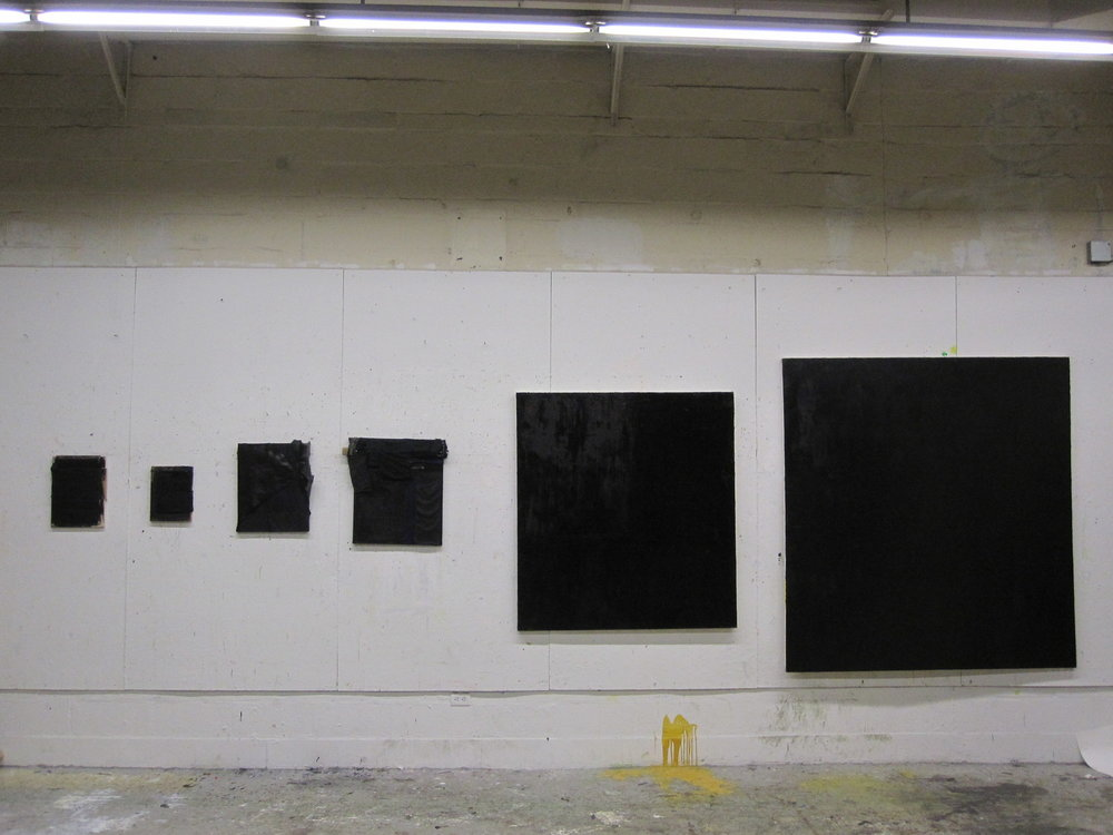 An installation shot of six predominantly black paintings taken at Rhode Island School of Design in 2011