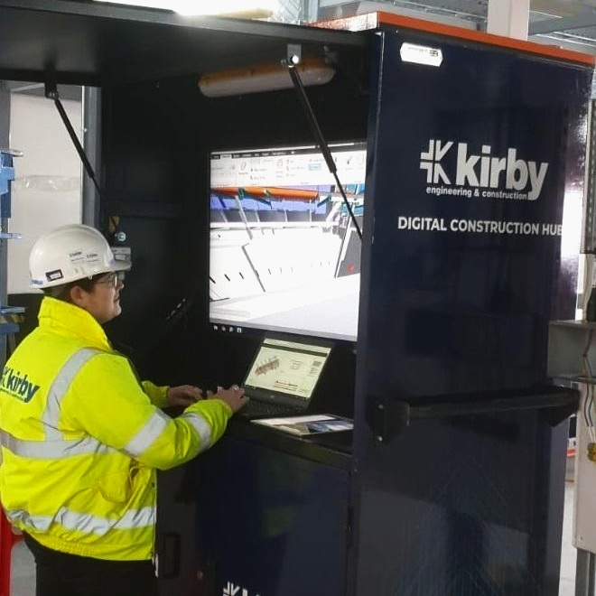 Kirby Engineering and Construction recently installed a Digital Construction Hub on site. This product is a real step towards a future of better BIM led digital communication for site teams.  Lead Mechanical and Electrical BIM Engineer, Stephanie Niland, photographed above, testing the new Hub on site.  The site team are reviewing the federated BIM model in the photograph below using Navisworks to navigate and preempt any possible service run clashes.  Photo credit: Kirby Group Engineering