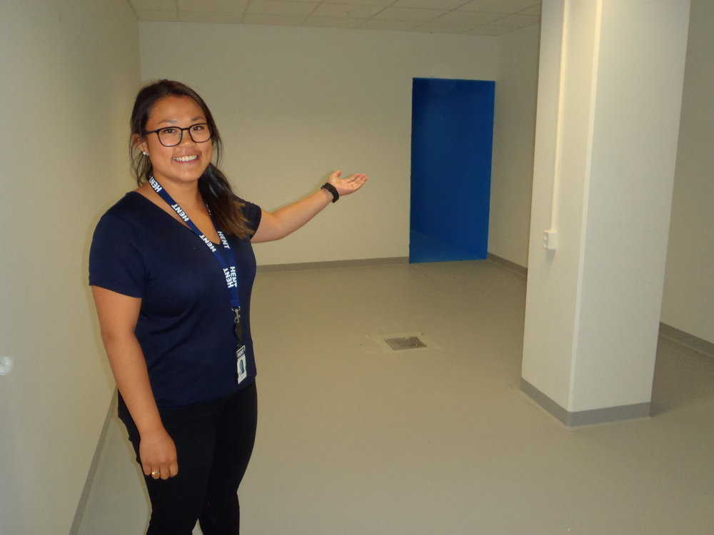 Prosjektingeniør Nina Njølstad viser oss en av de store garderobene. I bakgrunnen ser vi inngangen til dusjrommet i helblått.