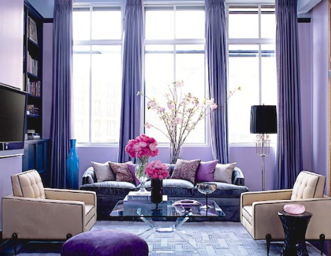 Love the deep purple and vibrant blue of the glass vase. The pastel cushions add a real softness.