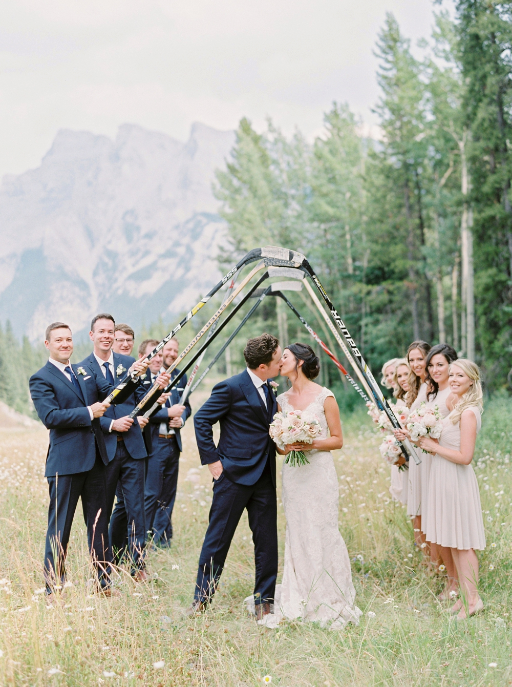 Canadian hockey wedding | wedding bridal party photograph with hockey sticks | Banff springs wedding photographers | fairmont banff rocky mountain wedding | Justine Milton fine art film Photography