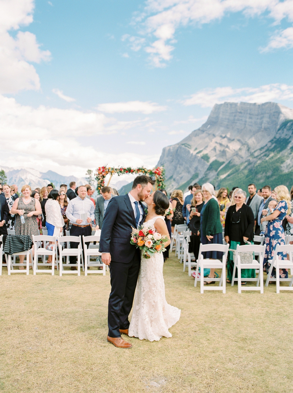 Banff Wedding Photographers | Banff tunnel mountain reservoir | wedding ceremony decor brightly colored floral arch | Justine Milton fine art film photographers