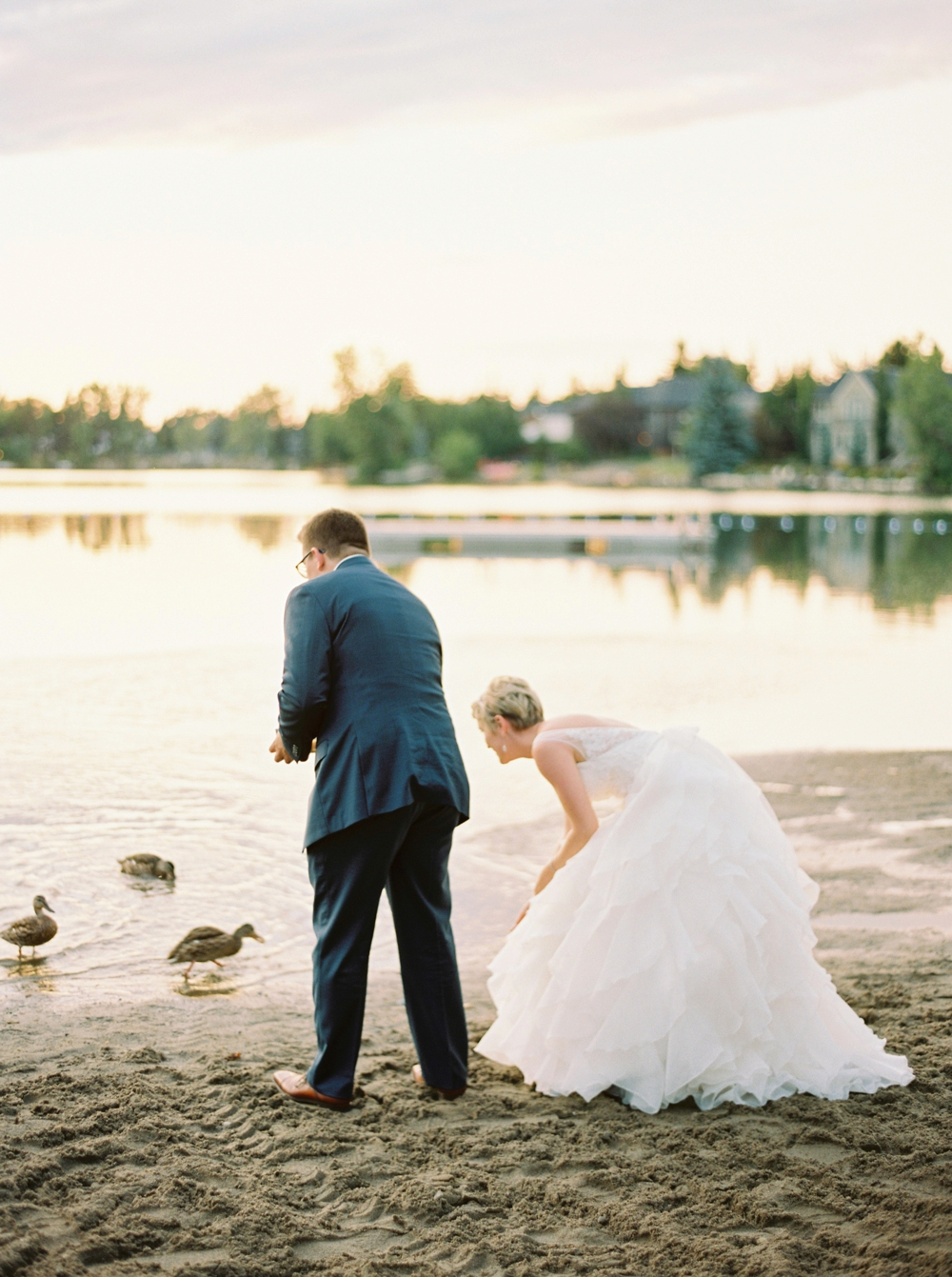 Calgary wedding photographers | The lake house wedding | The Lake House on Lake Bonavista Bride and groom photos with ducks | Justine Milton Photography