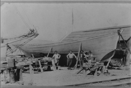 Four men in front of wooden boat Menotti Pasquinucci, an Italian immigrant, (holding hand saw) with newly built vessel and boatwrights, circa 1907.