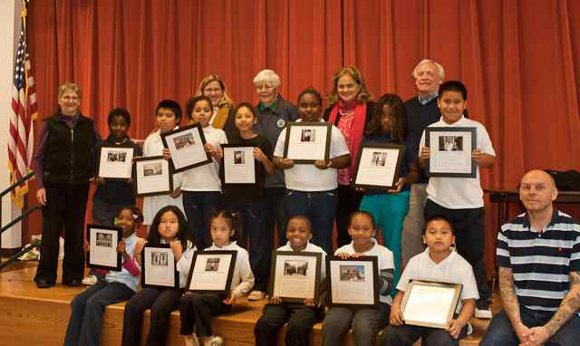 Bayside School third graders proudly display photos from their field trip, after receiving congratulations from teacher Paula Hammons(l.) and Historical Society members including Schools Program co-chairs Susan Frank (second from right, top row), and Bob Woodrum (bottom right).