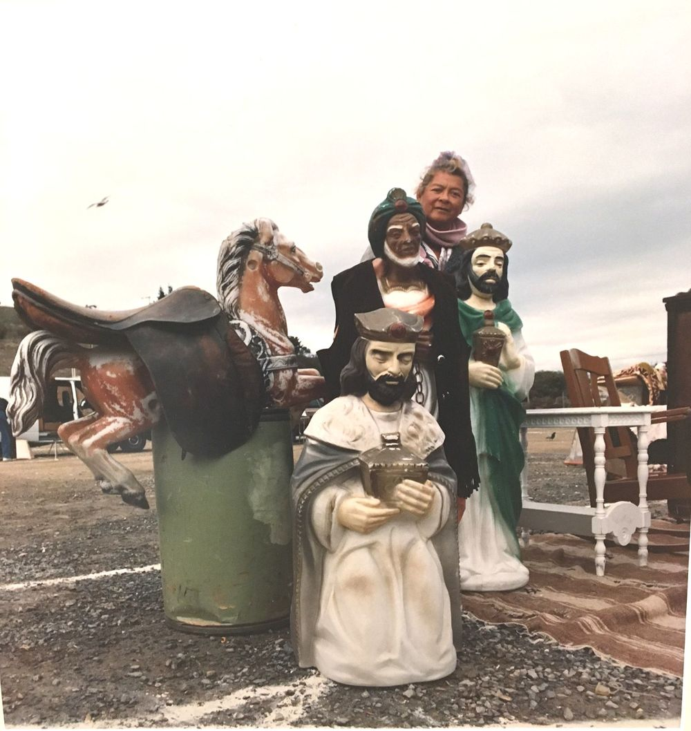 Flea market vendor surrounded by statues.  Photo by Nancy Kittle, courtesy of Anne T. Kent California Room, Marin County Free Library