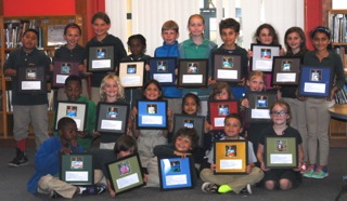 Willow Creek Academy students proudly display their end-of year awards presented to them by the Sausalito Historical Society. The framed award shows a picture of the student and a paragraph by them about their Sausalito history project.