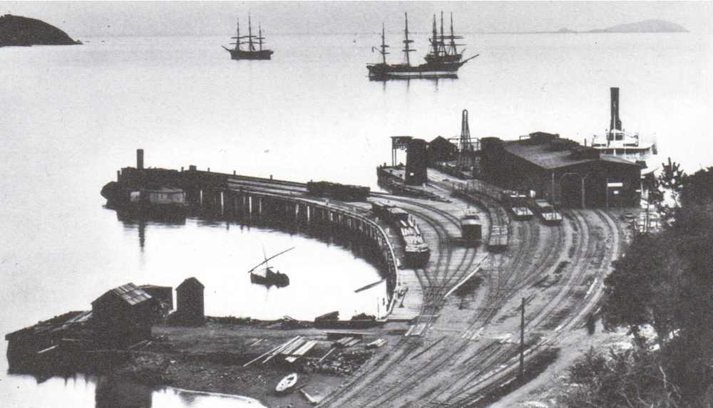 Sausalito rail and ferry wharf, with its narrow-gauge track, about 1890.  The ferry San Rafael is in the slip at right, and three square riggers ride at anchor offshore.