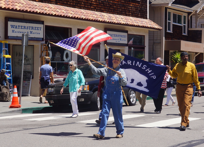 Madison Barker waves an American Flag while Tami Bell helps carry a Marinship banner in the Festa Parade     Photo   by Mike Moyle