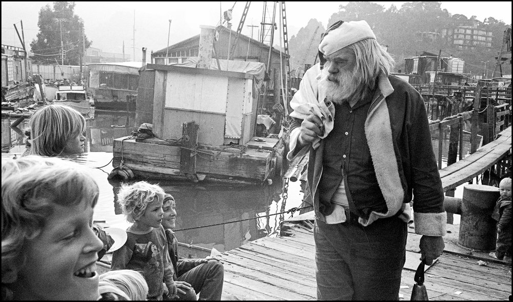 Santa (AKA Frank Anderson) visits the docks in the 70s in this image from Bruce's book.  Anderson was a local character who owned a nursery on Bridgeway.        ©Bruce Forrester