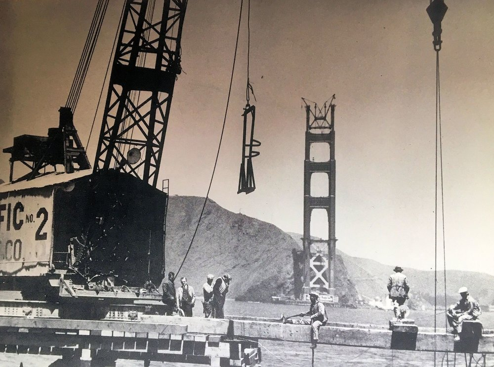 PHOTO COURTESY OF SAUSALITO HISTORICAL SOCIETY  In this photo from  Moments in Time , work continues on the San Francisco side of the bridge, while the Marin tower nears completion