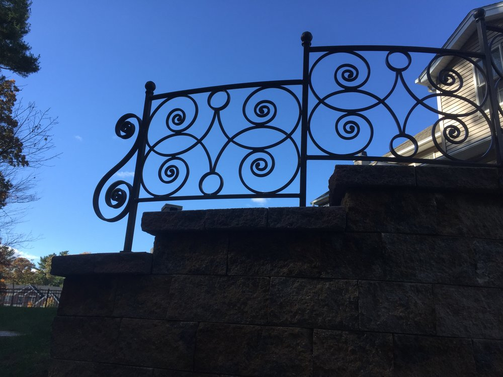 Hand-forged fencing on a retaining wall