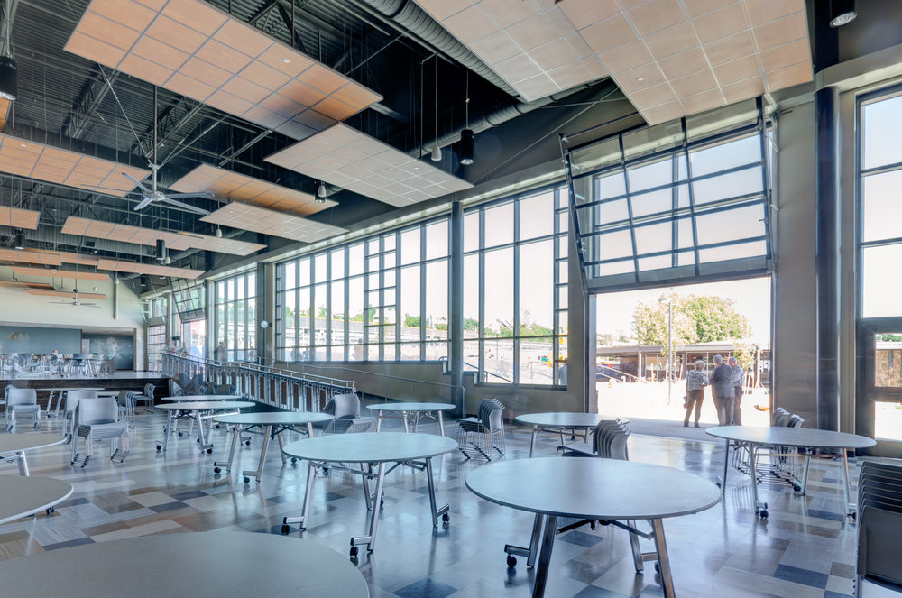 New student commons with access to natural light and the outdoors through use of glass garage doors.