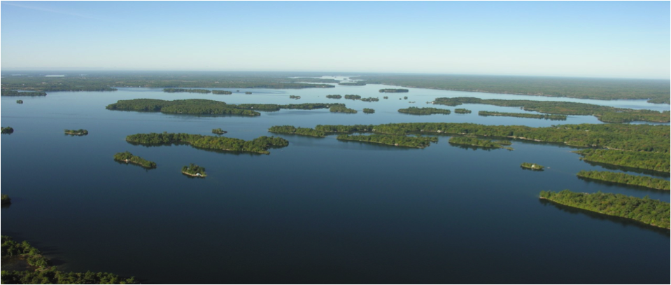 The Blue and the Green; the Paradise of The Big Rideau.  Looking westward toward the Narrows Lock seen in the distant centre near the horizon.  Note the lineation N.E. to S.W. of the islands in the foreground, a legacy from the Grenville Mountains a billion years ago and from the Pleistocene Ice Ages a mere million years ago. Further, this picture is testament that after two centuries of accelerated human impact, the blues and greens of Nature still dominate the Spirit of the Big Rideau.