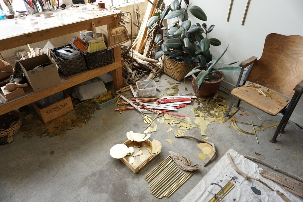 Process shot of brass scattered on the floor of Sarah's studio