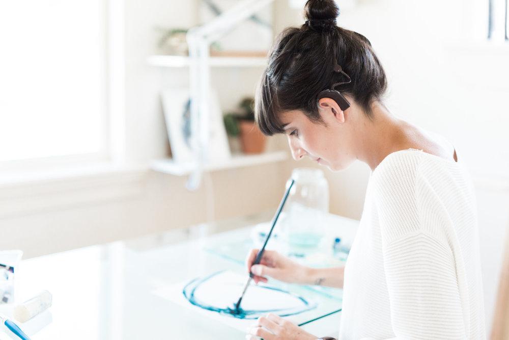 Kelsie Grazier painting in her studio