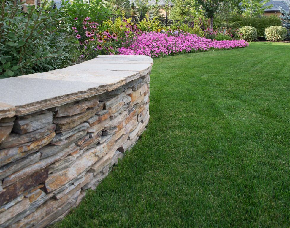 Curved natural stone wall by Platinum Landscape & Pools.