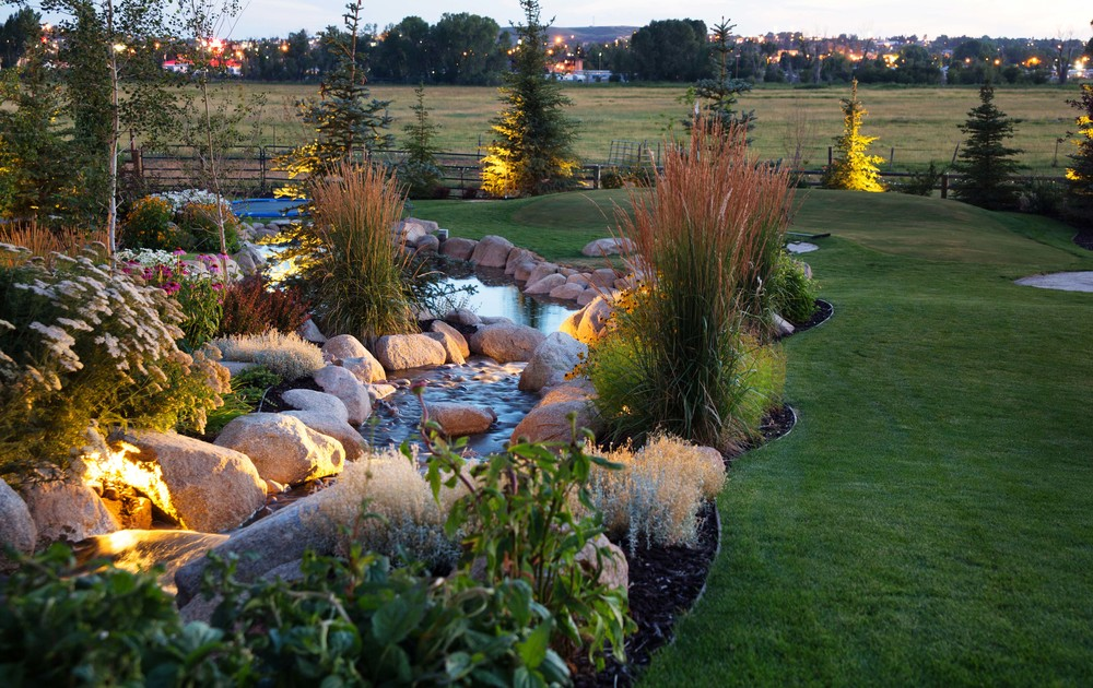 Water feature and stream with putting green by Platinum Landscape & Pools.