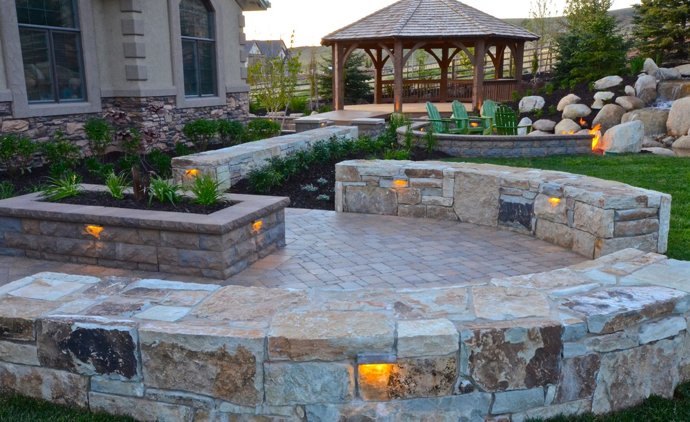 Curved stone seat walls and raised planter by Platinum Landscape & Pools.