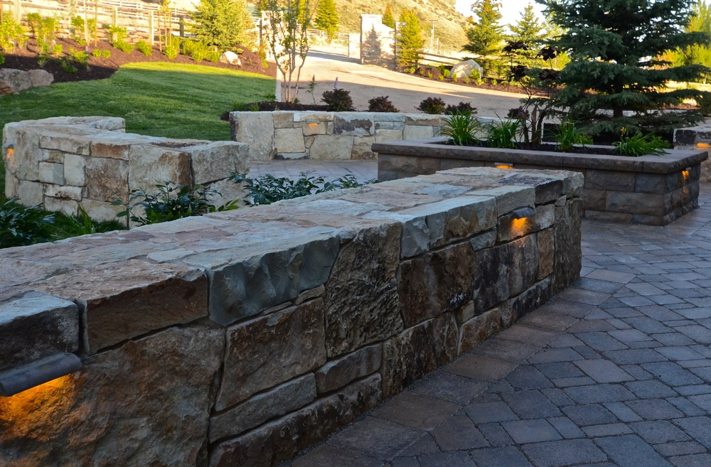Natural stone seat walls and Belgard pavers by Platinum Landscape & Pools.