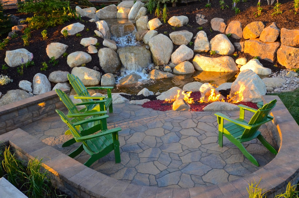 Water feature and Belgard sitting area by Platinum Landscape & Pools.
