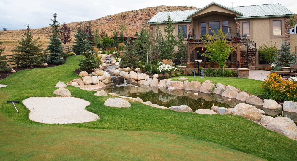 Putting green and water feature by Platinum Landscape & Pools.